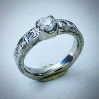 Half carat Canadian diamond set in 18K 601 white gold with hand engraving accents